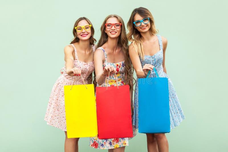 Portret van drie vrij gelukkige meisjes met pakketten met nieuwe kleren royalty-vrije stock fotografie