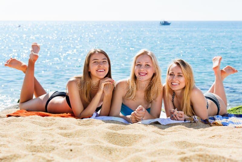 Portret van drie vrolijke jonge vrouwen op strand royalty-vrije stock foto