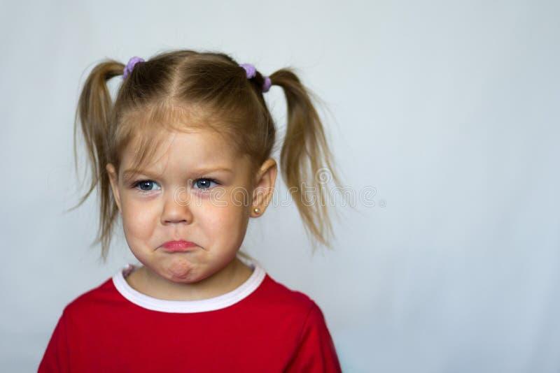 Portret van droevig meisje met blauwe ogen die opzij op witte achtergrond kijken royalty-vrije stock foto's
