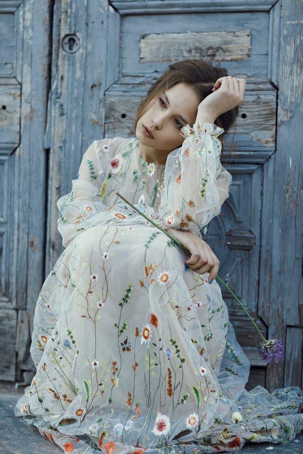 Portret van droevig meisje met mooi kapsel en kleding in de dagtijd _zitting meisje denken over iets en kijken opzij royalty-vrije stock afbeelding