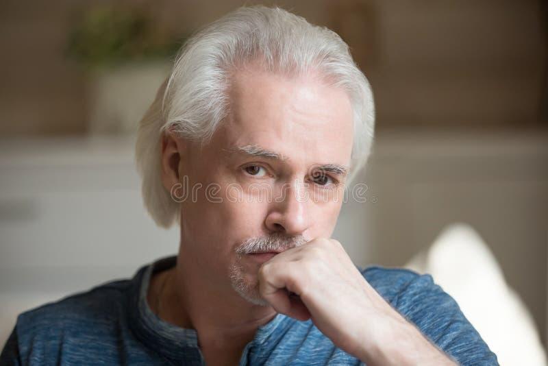 Portret van droevig oud mannetje die over iets nadenken stock afbeelding