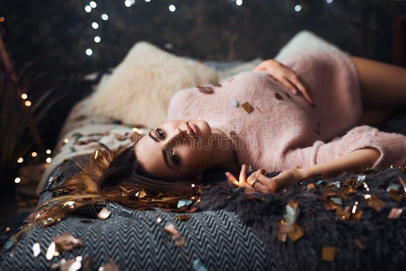 Portret van droevige aantrekkelijke jonge vrouw die met van de klatergoudconfettien en slinger lichten alonein donkere ruimte vie stock fotografie