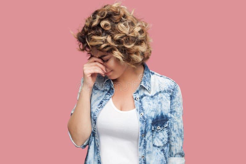 Portret van droevige alleen gedeprimeerde jonge vrouw met krullend kapsel in toevallig blauw overhemd die en hoofd beneden bevind royalty-vrije stock fotografie