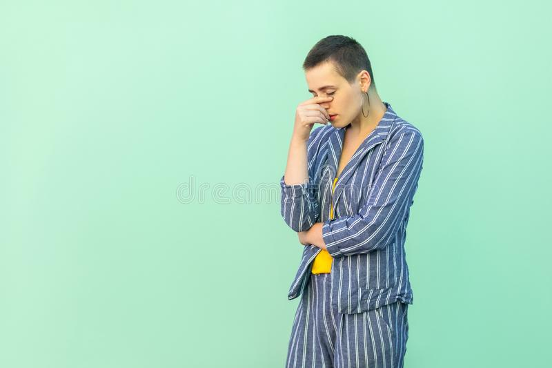 Portret van droevige gedeprimeerde korte haar jonge modieuze vrouw in toevallig gestreept kostuum die, hoofd beneden houden en of stock afbeelding