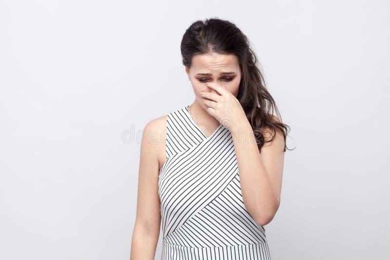 Portret van droevige gedeprimeerde mooie jonge donkerbruine vrouw met make-up en gestreepte kleding die, hoofd beneden houden en  stock fotografie