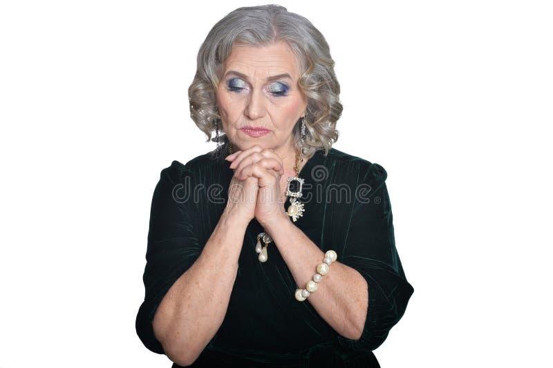 Portret van droevige hogere vrouw die zwarte blouse op witte achtergrond dragen stock foto