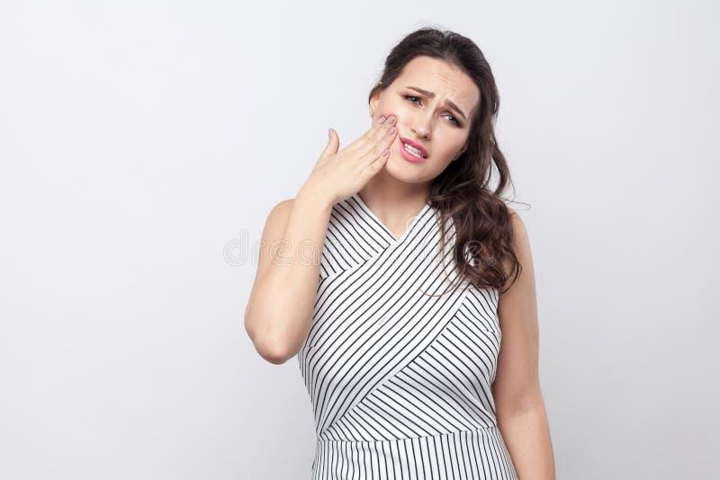 Portret van droevige ongelukkige mooie jonge donkerbruine vrouw met make-up en gestreepte kleding die rakend haar chik omdat gevo royalty-vrije stock afbeelding