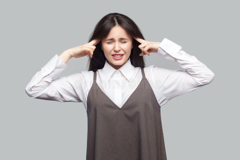 Portret van droevige verwarde mooie jonge vrouw in wit overhemd en bruine schort met make-up en donkerbruin haar die zich met hoo royalty-vrije stock fotografie