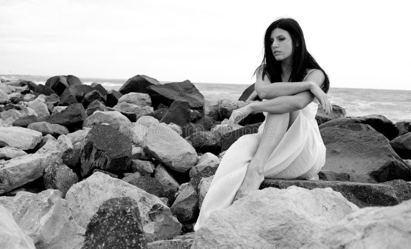 Portret van droevige vrouwenzitting op rotsen voor oceaan royalty-vrije stock foto's