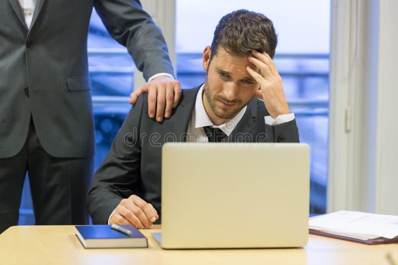 Portret van droevige zakenman met haar werkgever bij achtergrond Hand  royalty-vrije stock foto's