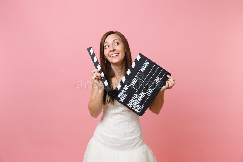 Portret van dromerige bruidvrouw die in huwelijkskleding omhoog greep klassieke zwarte film die clapperboard maken kijken royalty-vrije stock afbeeldingen