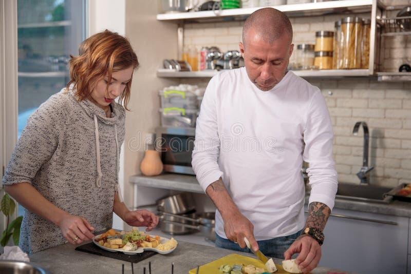 Portret van echtgenoot en vrouw die de kaas in de keuken cuting stock foto