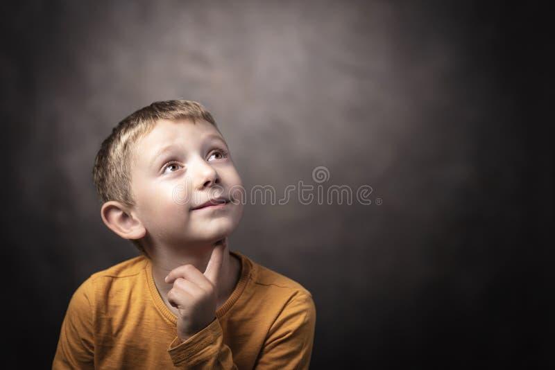 Portret van een 6 éénjarigenjongen die upwards met een nadenkende uitdrukking kijken royalty-vrije stock fotografie