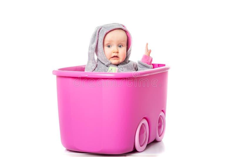 Portret van een aanbiddelijk babymeisje die uit het zitten in een roze doos plakken die konijntjeskostuum op witte achtergrond dr royalty-vrije stock afbeelding