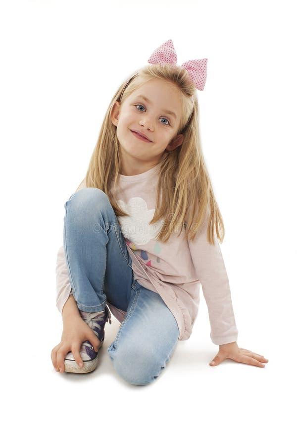 Portret van een aanbiddelijke meisjezitting op knie, het stellen stock afbeelding