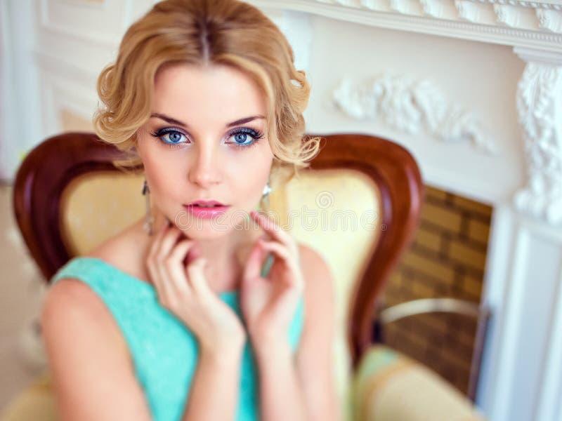 Portret van een aantrekkelijk blauw-eyed blonde in een blauwe kleding, clos stock foto