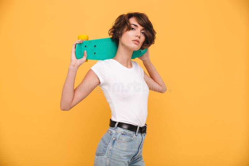 Portret van een aantrekkelijk jong skateboard van de meisjesholding stock afbeeldingen