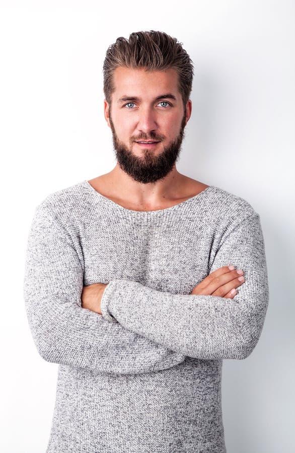 Portret van een aantrekkelijke die mens met een baard op een witte achtergrond met gekruiste wapens wordt geïsoleerd stock foto's