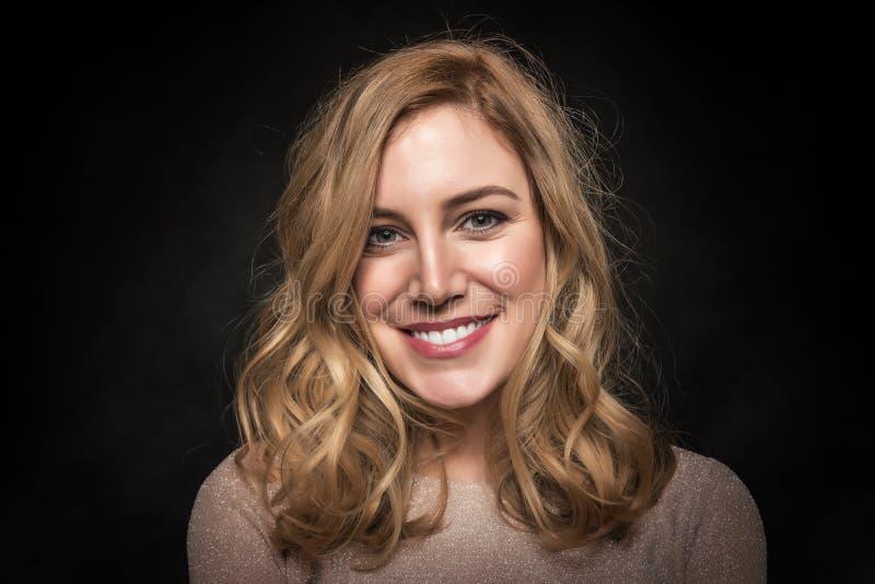Portret van een aantrekkelijke jonge blondevrouw op een zwarte achtergrond royalty-vrije stock foto's