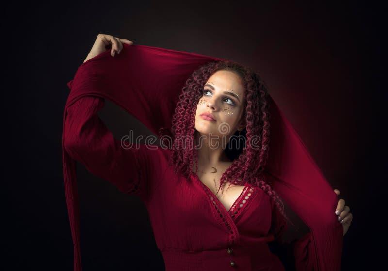 Portret van een aantrekkelijke jonge vrouw in een buitensporige rode kleding met een kap stock afbeelding