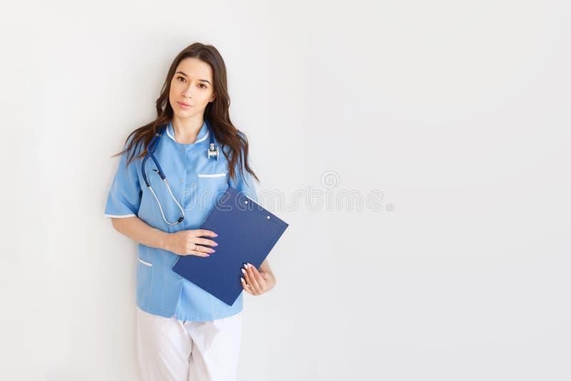 Portret van een aantrekkelijke jonge vrouwelijke arts in blauwe laag met copyspace stock afbeeldingen