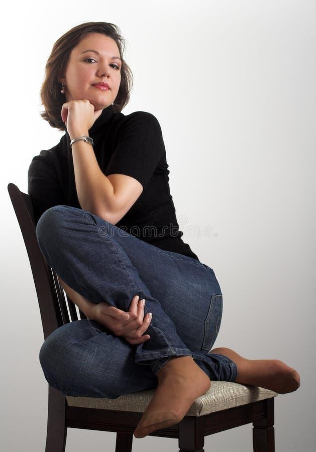 Portret van een aantrekkelijke jonge vrouwenzitting op een stoel royalty-vrije stock fotografie