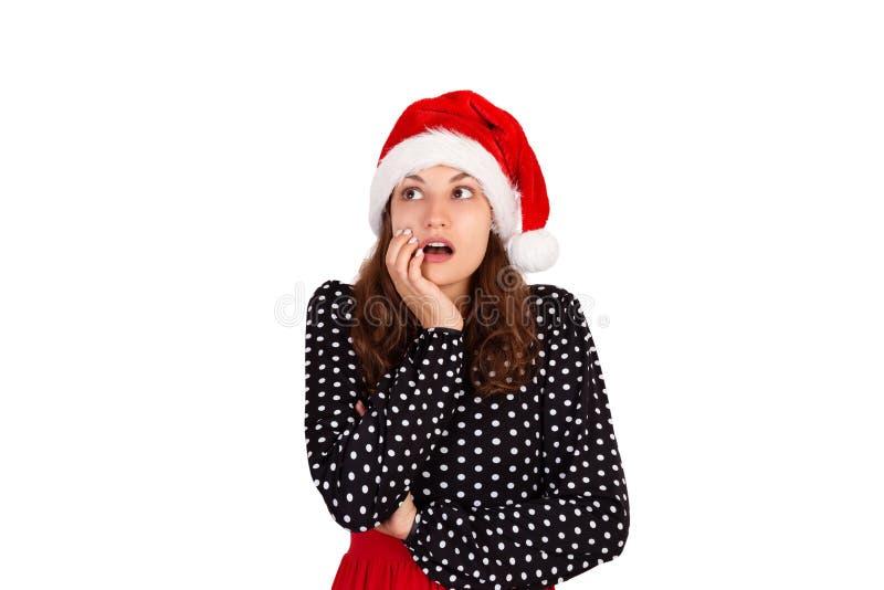 Portret van een aantrekkelijke nadenkende vrouw emotioneel meisje in Kerstmishoed van de Kerstman dat op witte achtergrond wordt  stock foto's