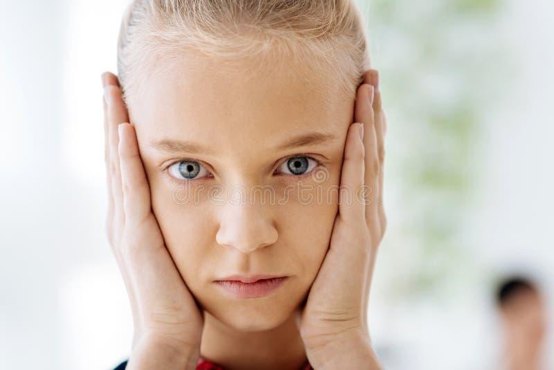 Portret van een aardig prettig meisje die haar wangen houden royalty-vrije stock afbeelding