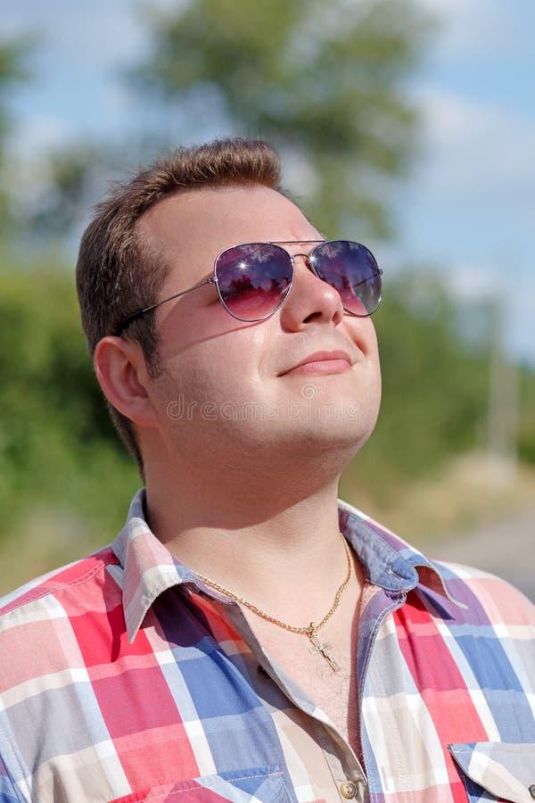 Portret van een aardige vriendschappelijke het glimlachen kerel in zonnebril Mensenportret in aard De kerel bekijkt de zon in gla stock foto's