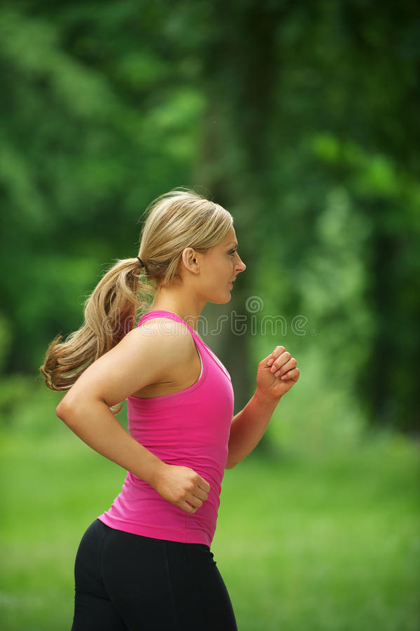 Portret van een actieve jonge blonde vrouwenjogging in het park stock fotografie