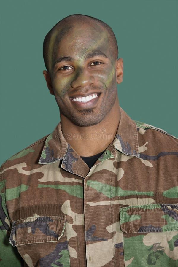 Portret van een Afrikaanse Amerikaanse mannelijke militair van de V.S. Marine Corps met gecamoufleerd gezicht over groene achtergr royalty-vrije stock foto's