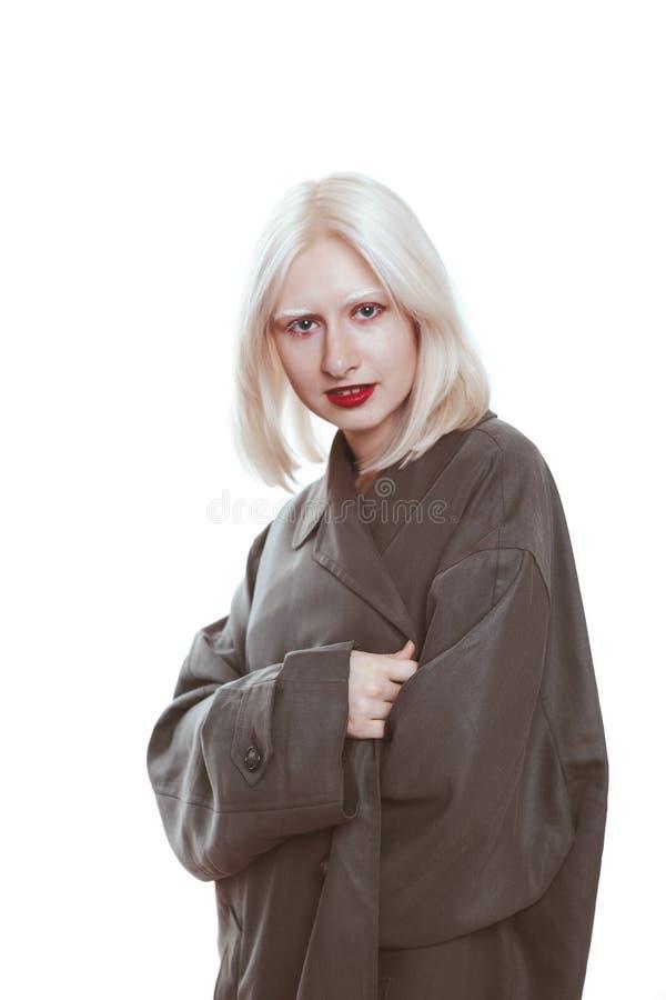 Portret van een albinomeisje in een regenjas in de studio stock foto's