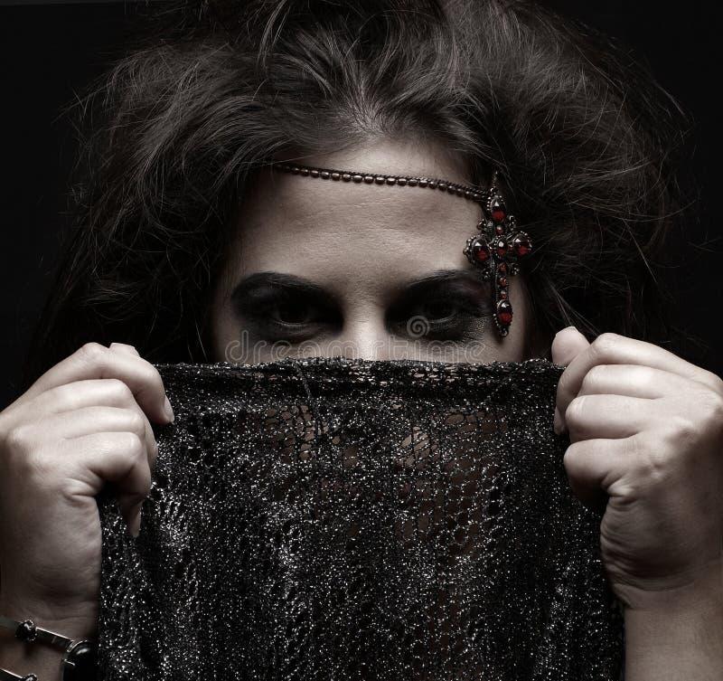 Portret van een Arabische vrouw die een donkere sjaal houdt stock foto's