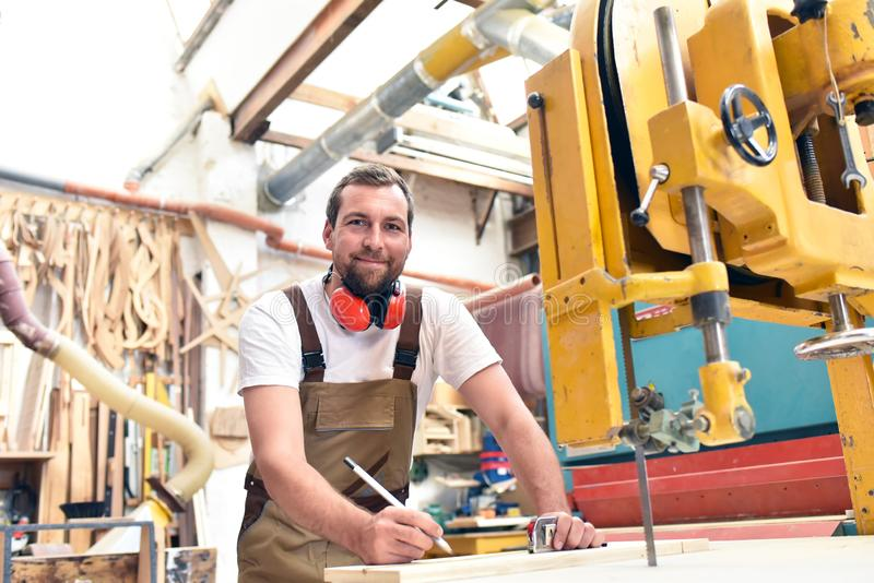 Portret van een arbeider in een schrijnwerkerij op het werk - houtbewerking stock foto