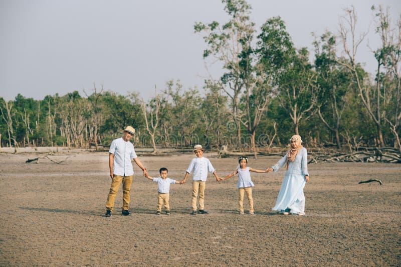 Portret van een Aziatische Maleise familie die zeer gelukkig samen in openlucht houdend hand kijken stock afbeeldingen