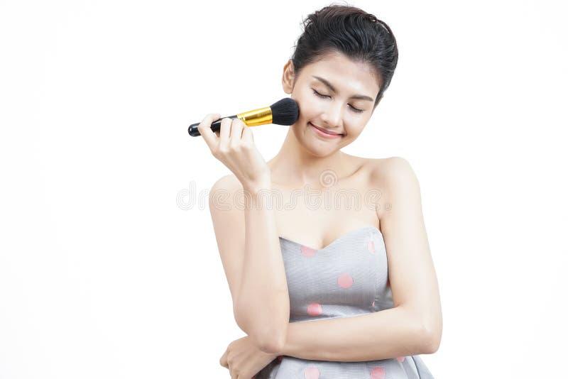 Portret van een Aziatische vrouw die droge kosmetische toon- stichting op het gezicht toepassen die make-upborstel op geïsoleerd  stock foto's