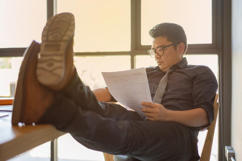 Portret van een Aziatische zakenman die en bij bureau ontspannen werken Hij zit in zijn bureau met benen op het bureau royalty-vrije stock foto's