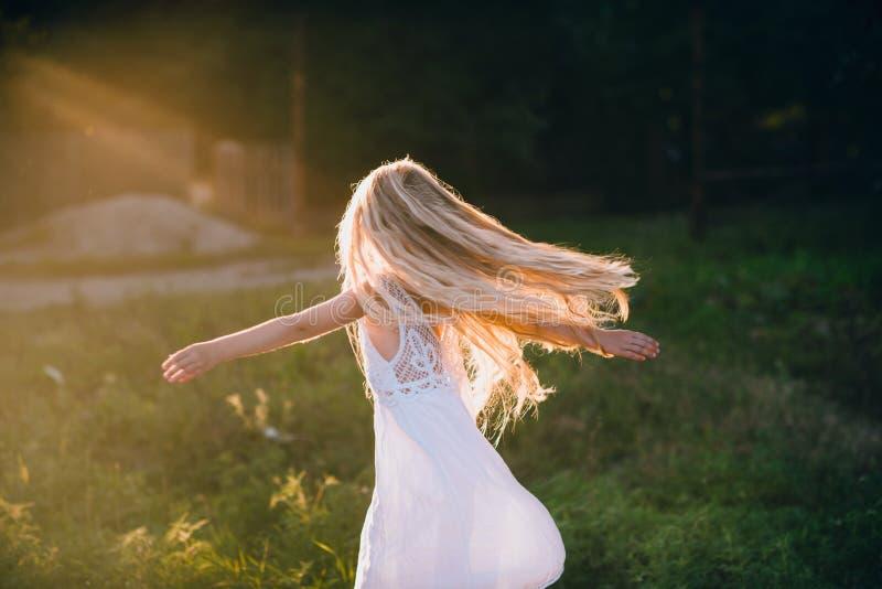 Portret van een babymeisje die op een gebied in zonsonderganglicht spinnen royalty-vrije stock afbeelding