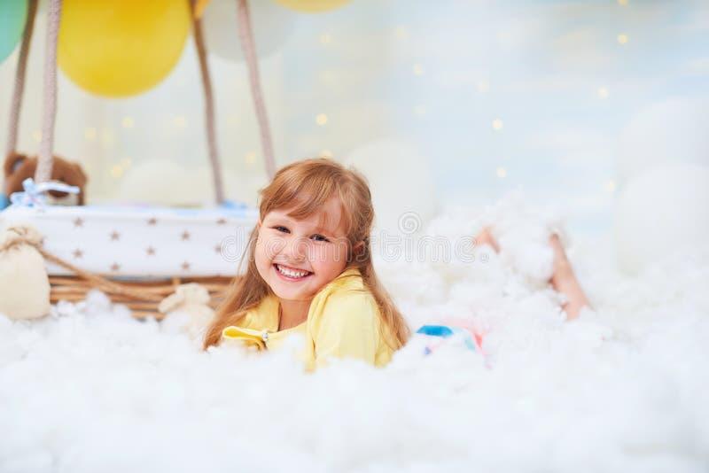 Portret van een babymeisje die op een wolk naast een en mand die van ballon in de wolken, in dromen liggen reizen vliegen stock foto's