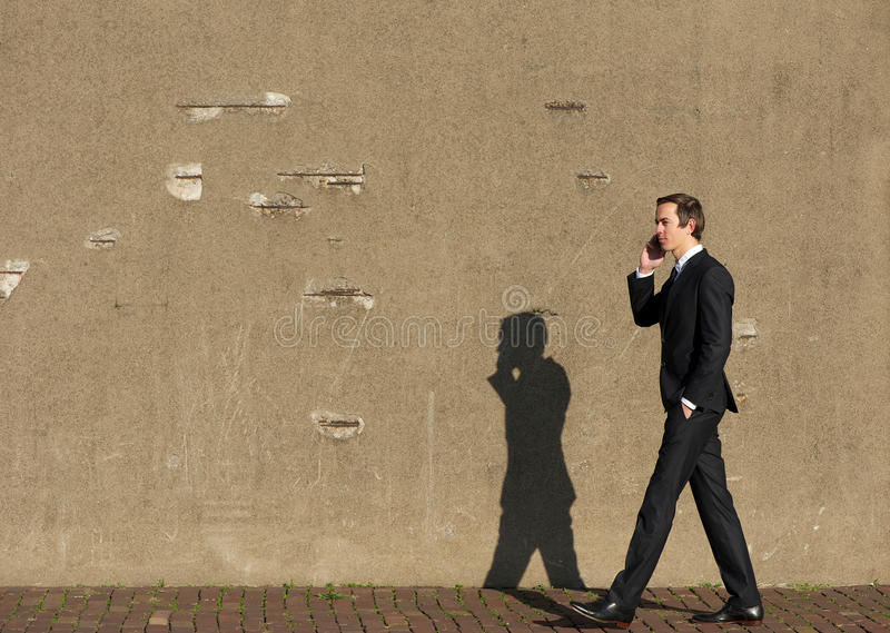 Portret van een bedrijfsmens die en op cellphone lopen spreken stock foto's