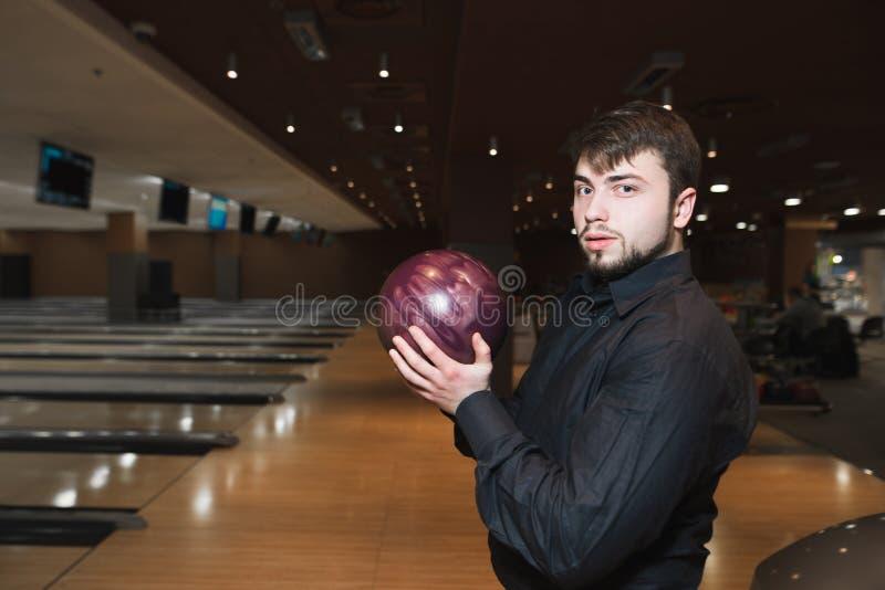 Portret van een bedrijfsmens met een kegelenbal in zijn handen tijdens het spel Rust in een kegelenspel stock afbeelding