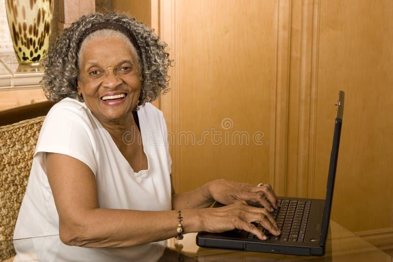 Portret van een bejaarde Afrikaanse Amerikaanse vrouw op haar computer stock foto