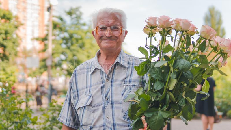 Portret van een bejaarde die zich op de straat met een boeket van rozen bevinden royalty-vrije stock foto