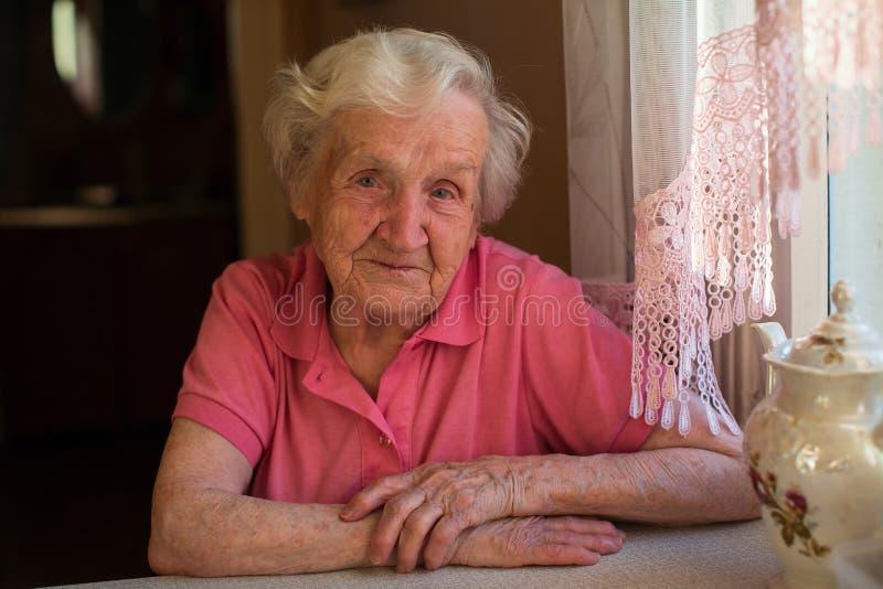 Portret van een bejaarde eenzame vrouw in haar huis stock foto's