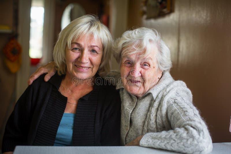 Portret van een bejaarde gelukkige vrouw met haar volwassen dochter stock afbeeldingen
