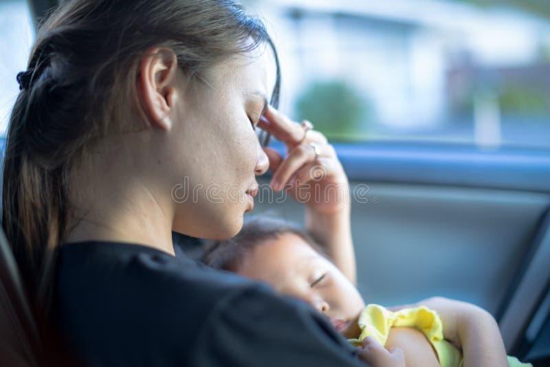 Portret van een beklemtoonde moeder die proberen het hoofd te bieden terwijl zij haar slaapbaby in haar wapens vervoert stock fotografie