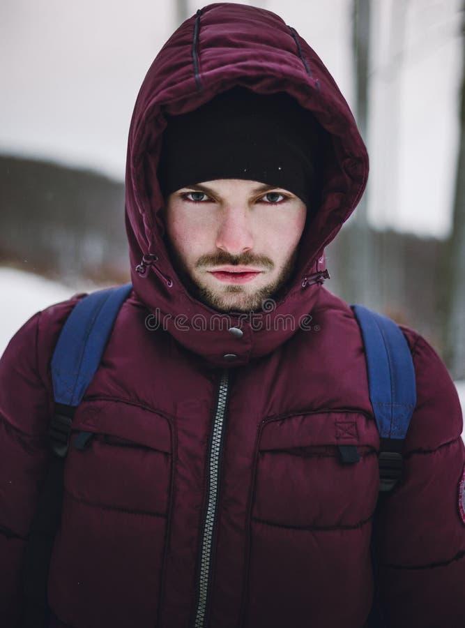 Portret van een bergbeklimmermens met rugzak in sneeuwblizzard Sluit van Hikerholding omhoog zijn pak in diep en bevroren bos bin royalty-vrije stock foto's