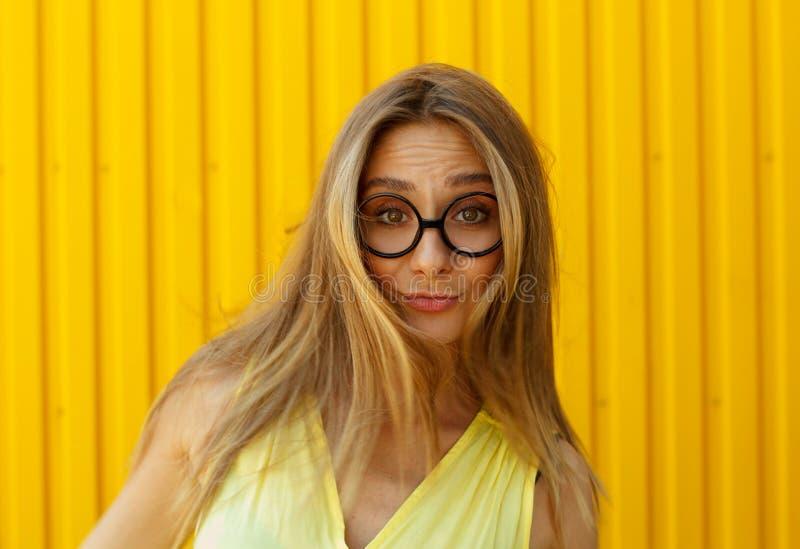 Portret van een blij meisje die stuk speelgoed grappige glazen over geel dragen stock afbeelding