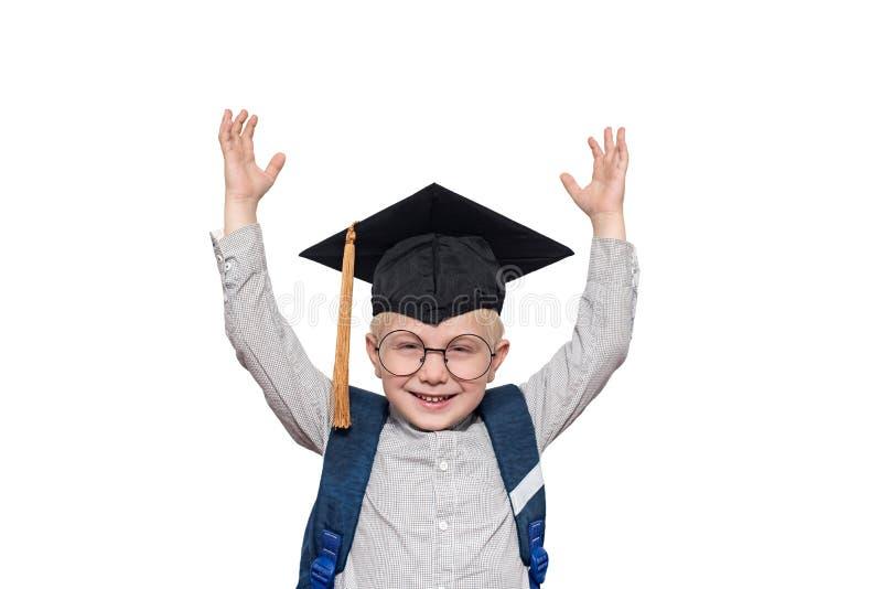 Portret van een blije blonde jongen in grote glazen, academische hoed en een schooltas Handen omhoog isoleer royalty-vrije stock afbeelding
