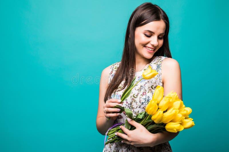 Portret van een blije jonge vrouw die in de zomerkleding geel die tulpenboeket houden over blauwe achtergrond wordt geïsoleerd stock foto